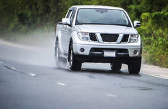 Truck driving in rain. White pick up truck driving fast in rain on wet road Stock Photos