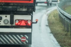 A truck is driving on the road in the rain Royalty Free Stock Photos