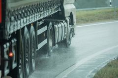 A truck is driving on the road in the rain Royalty Free Stock Photo
