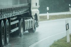 A truck is driving on the road in the rain Stock Photography