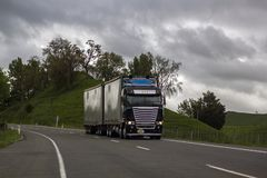 Truck driving on road in rural landscape