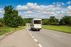 Truck driving on the road. White truck driving along the straight country-road at summer time Royalty Free Stock Photography