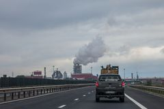 Truck driving on a Romanian motorway near the road of Sebes, a highly polluting wood processing factory can be seen in background stock photo
