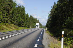 Truck driving a scenic country route. Truck driving on a scenic country highway, surrounded by trees and forest Stock Photo
