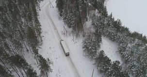 Truck driving on winter country road in snowy forest. Aerial footage. stock footage