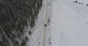 Truck driving on winter country road in snowy forest. Aerial footage. stock video