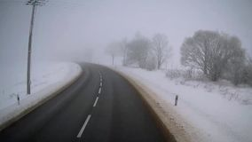 Truck driving on winter foggy road. Exclusive view from the cab of a truck driver. Accelerated ride on empty road in foggy winter day stock video footage