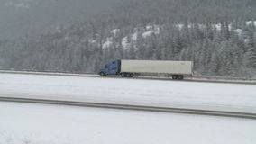 Truck driving in winter snow conditions. Truck driving on the highway during icy winter road conditions stock video footage
