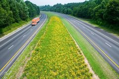 Truck driving on yellow flower lined state highway in rural Virginia Stock Images