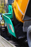 Truck dumping asphalt to running paving machine Royalty Free Stock Image