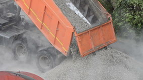 Truck dumping sand and gravel mix on the road. Machine pour out stones on the way. Large industrial machine pour gravel. On the street. The dump truck unloads stock video footage