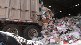 A Truck Dumps Trash to be Recycled (3 of 10). Trash being delivered at the recycling center stock footage