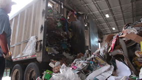 A Truck Dumps Trash to be Recycled (5 of 10). Trash being delivered at the recycling center stock video footage