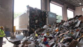 A Truck Dumps Trash to be Recycled (4 of 10). Trash being delivered at the recycling center stock video footage