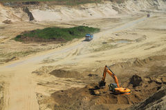 Truck and excavator in a quarry in sunny day. POLEWOJE, KALININGRAD REGION, RUSSIA — JUNE 18, 2014: Truck and excavator in a quarry in sunny day Royalty Free Stock Photos