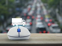Truck transportation service concept. Truck flat icon with wireless computer mouse on wooden table over blur of rush hour with cars and road, Business Royalty Free Stock Photography