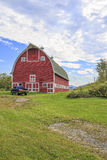 Truck in front of classic old red barn in Vermont. A beautiful red barn in the state of Vermont Royalty Free Stock Image