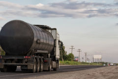 Truck with fuel tanker at road. A truck hauling a fuel tanker along the asphalt road out of town Royalty Free Stock Photos