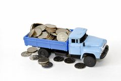 A truck full of money. An old truck body that is filled with coins, the coins are lying around and under the truck, everything is on a white background stock photography