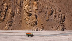 Truck full of stuff driving in watercourse in low water season. Huge textured brown rocks background. Annapurna circuit trekking route. Nepal Stock Photo