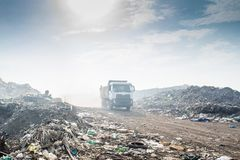 Truck at the garbage dump full of smoke, litter, plastic bottles,rubbish and trash at the Thilafushi local tropical island Stock Image