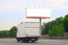 Truck goes on highway by billboard Stock Image