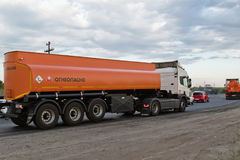A truck hauling a fuel tanker on bypass road. VOLGOGRAD - JULY 30: A truck hauling an orange fuel tanker on bypass road. July 22, 2016 in Volgograd, Russia Royalty Free Stock Photo