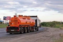 A truck hauling an orange fuel tanker on bypass road. VOLGOGRAD - JULY 30: A truck hauling an orange fuel tanker on bypass road. July 22, 2016 in Volgograd Stock Image