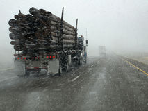 Truck Hauling Wood Driving in Snow Storm Stock Photo