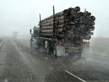 Truck Hauling Wood Driving in Snow Storm Stock Image