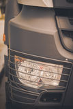 Truck headlight detail. Close up image of a truck headlight with a protective grille Stock Photo