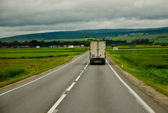 Truck on highway. Truck on a country highway under the clouds , rear view Stock Photos