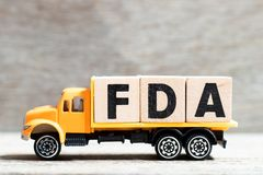 Truck hold letter block in word FDA abbreviation of food and drug administration on wood background