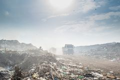 Truck at the huge garbage dump full of smoke, litter, plastic bottles,rubbish and trash at the Thilafushi local tropical island Royalty Free Stock Photography