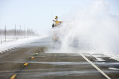 Truck kicking snow on road. Stock Photos