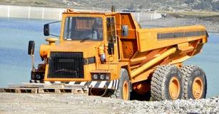 Truck lakeside. Shipyard construction excavator truck truck tire factory job lake road transport man Royalty Free Stock Photo