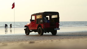 Truck leaving the sandy beach, with man passing. stock footage