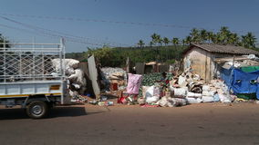 Truck leaving after unloading sacks with waste at the disposal place. GOA, INDIA - 26 JANUARY 2015: Truck leaving after unloading sacks with waste at the stock video footage