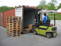 Truck Lifting Pallet Out Of Container Stock Photography