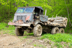 Truck loaded with logs. Old wrecked truck loaded with logs in a forest Stock Photo