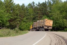 A truck loaded with timber standing on the road in the forest. In summer Stock Image