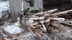 Truck loader crane arm picks up sawmill wooden waste. On cold winter day, lots of snow and sawdust stock video