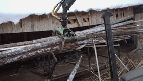 Truck loader crane claw lifts up sawmill wooden waste. On cold winter day, lots of snow and sawdust stock video footage