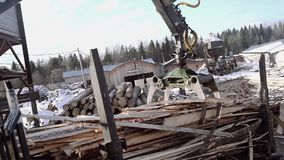 Truck loader crane claw picks up sawmill planks waste. On cold winter day, lots of snow and sawdust stock footage