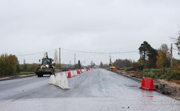 Truck loader is driving on the new repaired asphalt road with plastic enclosures. Truck loader is driving on the new repaired asphalt road with plastic stock photography
