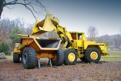Truck loading. Excavator bulldozer load big truck Royalty Free Stock Images