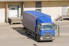 Truck loading goods, cargo, warehouse with doors. Truck loading goods, cargo, warehouse with doors Royalty Free Stock Images