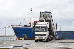 Truck loading grain on ship Stock Images