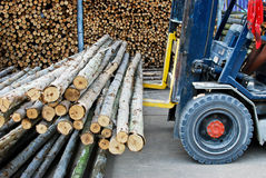 Truck loading pile of wood in logs storage. For construction or industrial work royalty free stock images