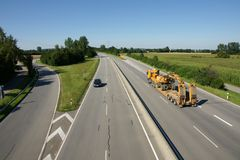Truck on modern highway. A view of a heavy construction truck hauling an excavator on an open, modern multi-lane highway Stock Photo